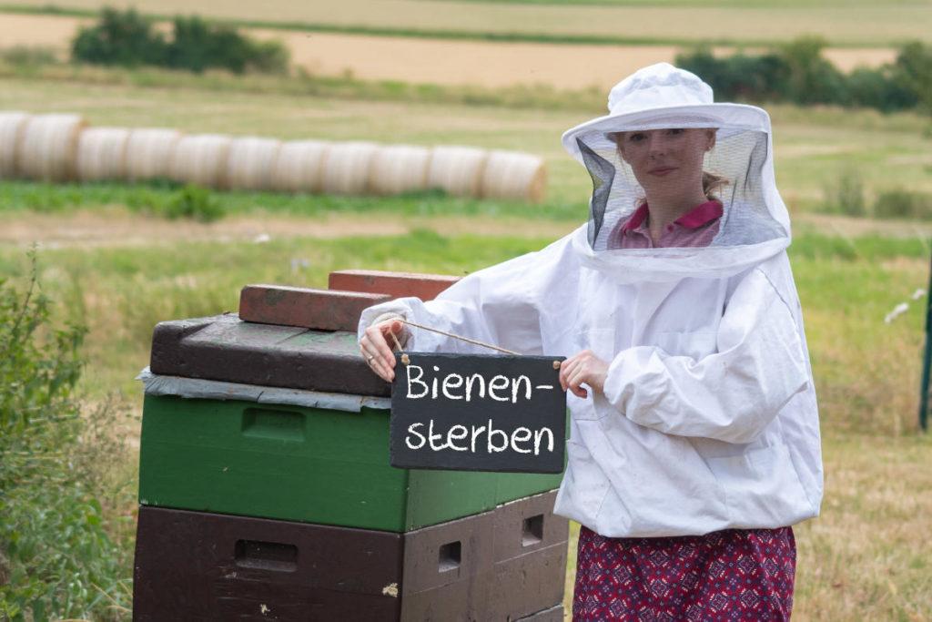 Imkerin hält Kreidetafel mit dem Wort Bienensterben hoch